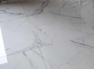 Gepolijst vloertegel 90×90 cm marmerlook Carrara wit Nr. 56 op de vloer geplaatst is mooi op de vloer en wand.