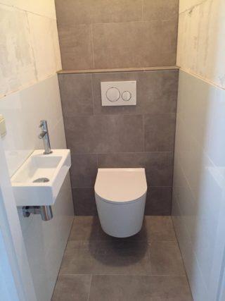 Vloertegel 30×60 cm Ariel Grijs betonlook NR12 op het toilet. Deze tegel is ook leverbaar in 60x60 cm en 80x80 cm.