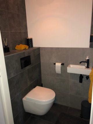 Vloertegel 30×60 cm Betonlook Ariel Antraciet NR 20 op het toilet