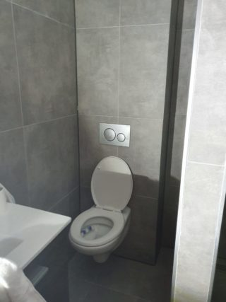 Vloertegel 60×60 cm Ariel Grijs betonlook Nr. 12 achter de wc op de wand gelegd