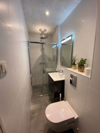 Vloertegel 60×60 cm Maddof Antraciet betonlook NR99 in de badkamer gecombineerd met wandtegel mat wit 30x60 cm