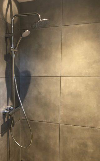 Vloertegels 60x60 cm betonlook antraciet opa 15 gebruikt als wandtegels in de badkamer