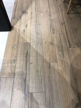 Keramisch parket 20x120 walnoot bruin met zwarte noesten niet van echt hout te onderscheiden op de vloer