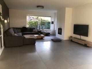 Betonlook grijs vloertegels 75x75 cm in de woonkamer gelegd